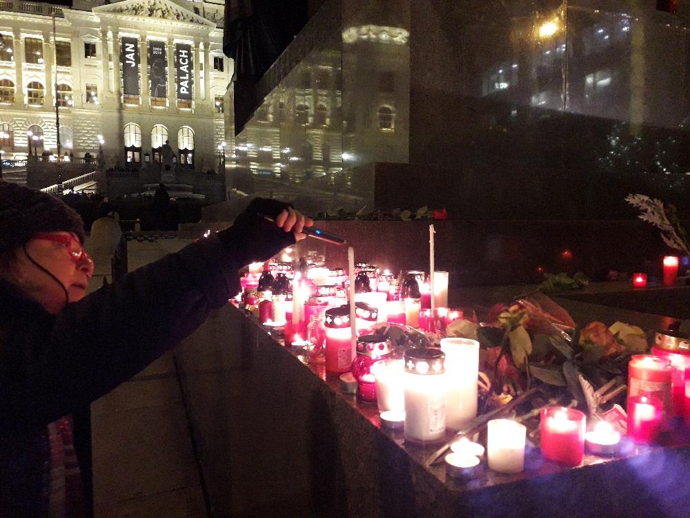 Eine Frau entfacht eine Kerze für Jan Palach und Jan Zajíc. Beide zündeten sich vor 50 Jahren auf dem Wenzelsplatz an.