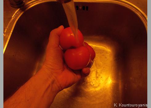 Waschen Sie die Tomaten mit kaltem Wassern und vierteln Sie sie. Geben Sie sie anschließend in die Salatschüssel.